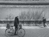 снимка в сивата скала на жена, стояща до велосипед близо до тялото
