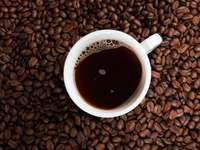 tazza in ceramica bianca su chicchi di caffè