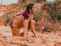 жена в кафяви панталони, седнала на кафяв пясък през деня