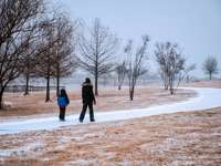 pessoa de casaco preto em pé no chão coberto de neve