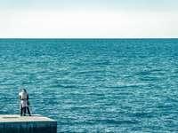 άντρας σε μαύρο σακάκι που κάθεται σε τσιμεντένιο πάγκο κοντά στη θάλασσα