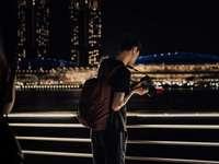 muž v černé bundě a kalhotách stojící na chodníku