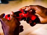лице, което държи червен и черен контролер за игра