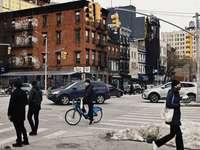 man in black jacket and black pants walking on sidewalk