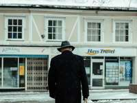 човек в черно палто, ходещ по заснежена земя