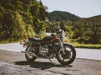черен и сребърен мотоциклет по сив асфалтов път