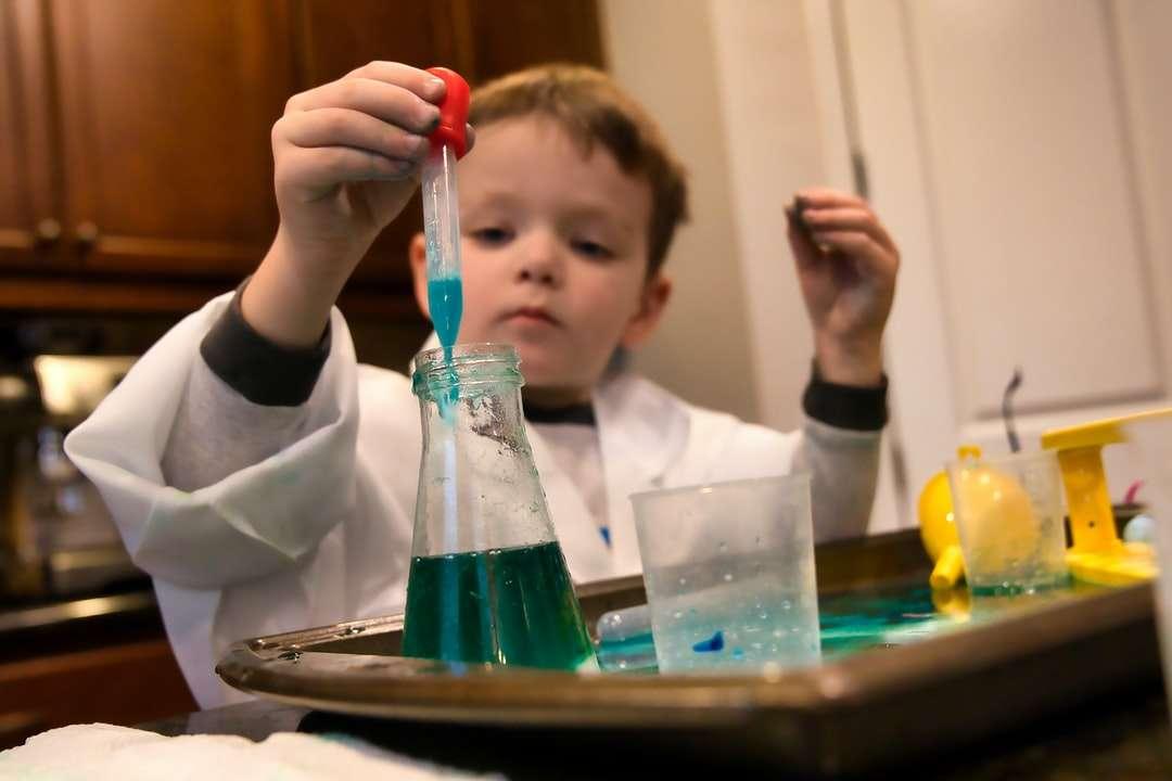 jongen in wit overhemd met lange mouwen - jongen in wit shirt met lange mouwen met rood en doorzichtig plastic gereedschap. Een jonge wetenschapper in het laboratorium (19×13)