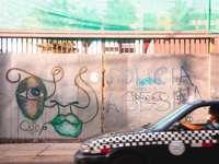 svart bil parkerad bredvid vit och blå vägg med graffiti
