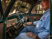 muž v modrém tlačítko nahoru tričko řízení auta během dne