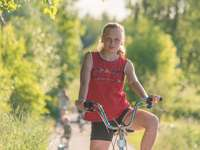 girl in red tank top riding on bicycle during daytime