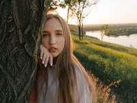 meisje in wit overhemd leunend op boom