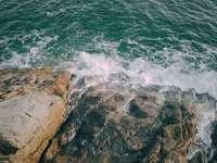 montanha rochosa marrom ao lado do corpo d'água durante o dia