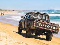 SUV preto na areia marrom perto do corpo d'água durante o dia