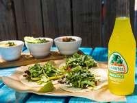 zöldségsaláta fehér kerámia tál mellett narancssárga üveg