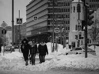 foto em tons de cinza de 2 pessoas caminhando em terreno coberto de neve