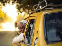 мъж в бяла риза с дълъг ръкав, стоящ до жълта кола