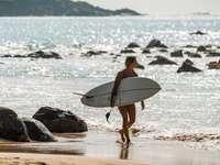 femme en bikini noir tenant planche de surf blanche