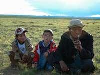 2 fiú ül a zöld füves területen napközben