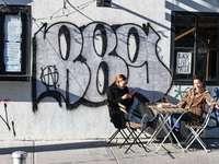 fekete kabátos férfi ült a fal mellett összecsukható szék