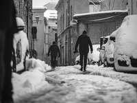 мъж в черно яке, ходещ по заснежен път