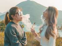 kvinna i vit långärmad skjorta som röker bredvid kvinnan