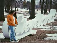 žena v oranžové bundě a modré džínové džíny