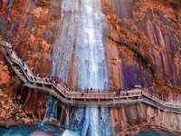 mensen lopen op bruine houten brug over watervallen
