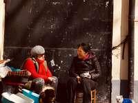homme en veste noire assis sur une chaise à côté de la femme