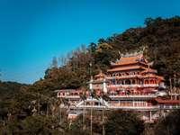 biało-czerwona świątynia otoczona zielonymi drzewami