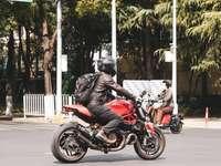 мъж в червено яке, каращ червен мотоциклет по пътя