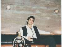 muž v černém kabátě sedí na hnědé dřevěné lavici