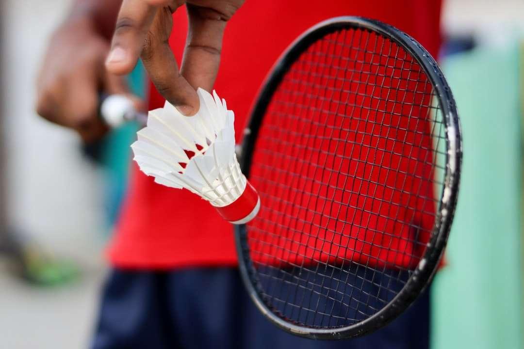 personne tenant une raquette de tennis rouge et noire - Joueur de badminton tenant une raquette avec volant de badminton (3×2)