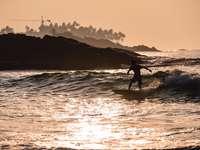 silueta unei persoane care navighează pe mare în timpul apusului