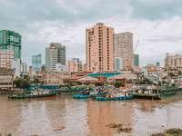 синя и бяла лодка по вода близо до градските сгради