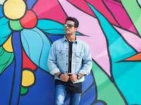 Homme en denim bleu veste boutonnée debout à côté du mur