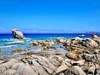 roci maronii pe mare albastră sub cer albastru în timpul zilei