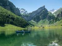Barco verde en el lago cerca de montañas verdes durante el día