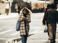 kvinna i vit och svart kappa som går på trottoaren