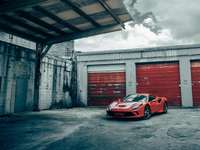 red and white porsche 911 parked beside gray concrete building