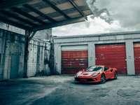 Porsche 911 rossa e bianca parcheggiata accanto a un edificio di cemento grigio
