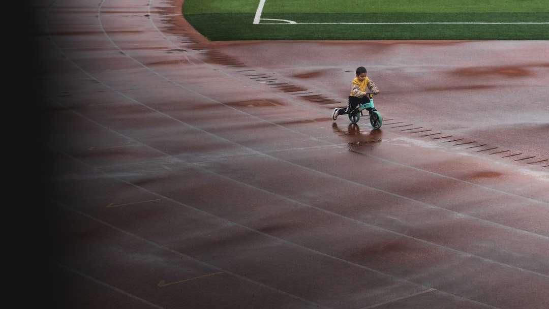 Junge im blauen Hemd, das Fahrrad auf Schienenfeld fährt - Junge im blauen Hemd, das Fahrrad auf Schienenfeld während des Tages reitet (8×5)