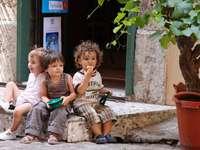 2 garçons et fille assise sur un banc en béton