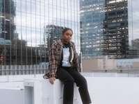 kvinna i svarta byxor som sitter på vit betongbänk