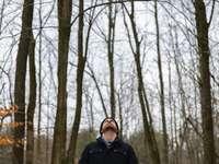 fekete kabátos férfi áll a csupasz fák közepén