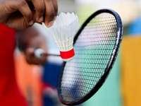 Person, die Schwarzweiss-Tennisschläger hält