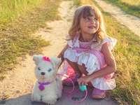 момиче в розова и бяла рокля с бяло куче плюшена играчка