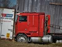 camion de marfă roșu și alb pe câmpul de iarbă verde