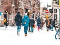 хора, ходещи по заснежен път през деня