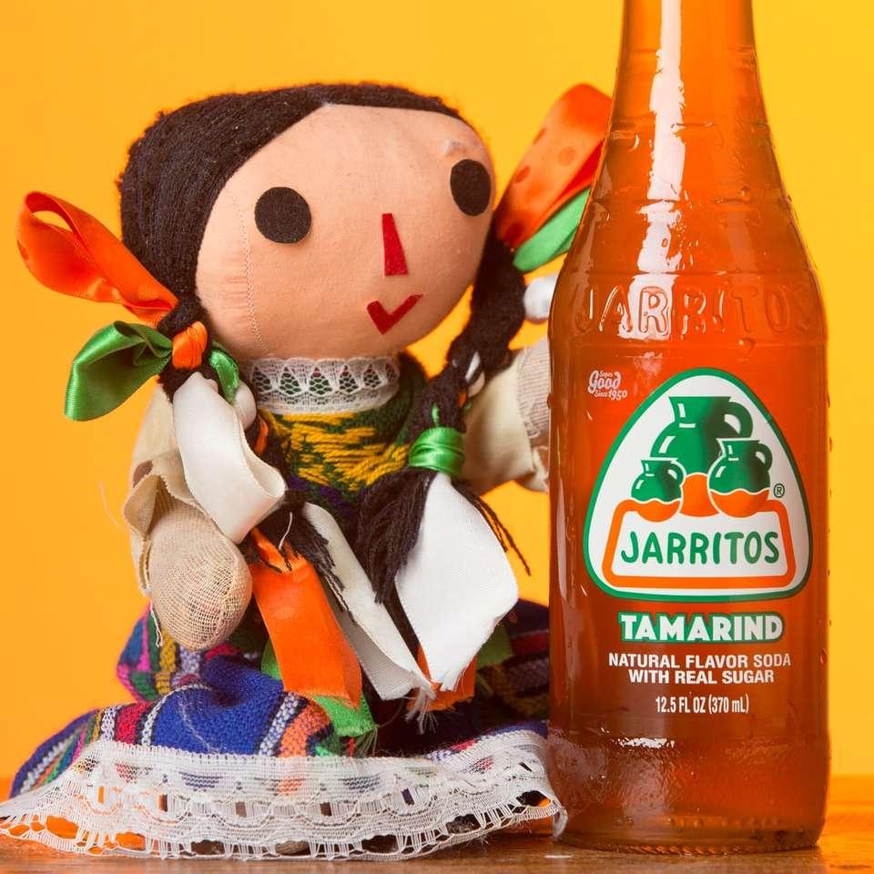 oranžová a bílá plastová láhev vedle plyšové hračky medvěda hnědého - Jarritos Tamarind a panenka Maria (3×3)