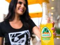 kobieta w czarnym podkoszulku trzymając butelkę soku pomarańczowego